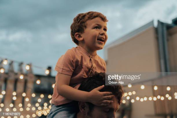 boy at a party with lights on background - christmas scenes stock pictures, royalty-free photos & images