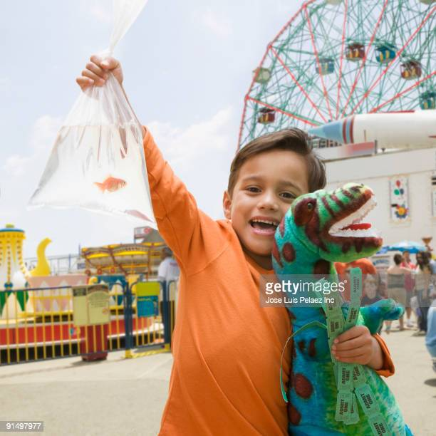 Boy at amusement park with stuffed dinosaur and goldfish