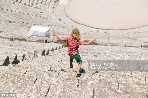 boy at ancient theater of epidaurus in greece - ancient greece photos stock pictures, royalty-free photos & images