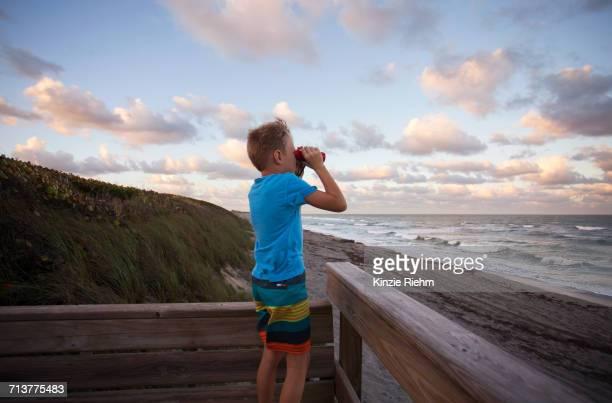 boy at beach looking at view through binoculars, blowing rocks preserve, jupiter, florida, usa - jupiter island stock photos and pictures