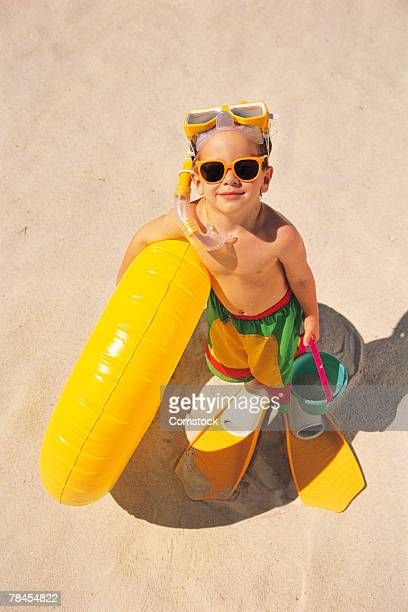 Boy at beach with snorkeling gear and yellow inner tube