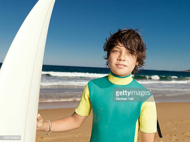 Boy at beach with surfboard