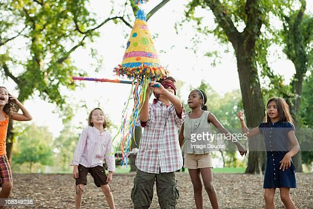 Boy at birthday party hitting pinata