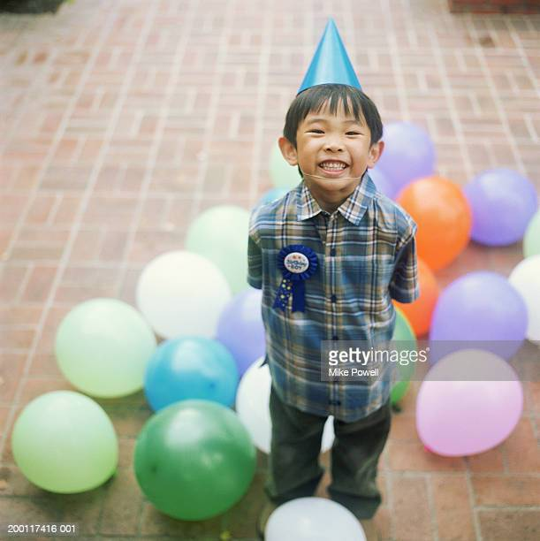 Boy (5-7) at birthday party, wearing party hat, portrait