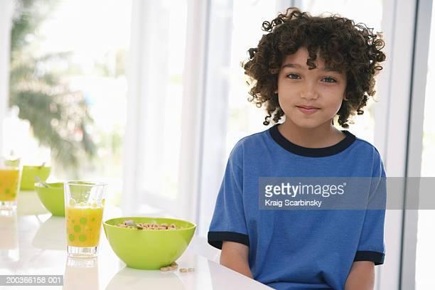 Boy (8-10) at breakfast table, portrait