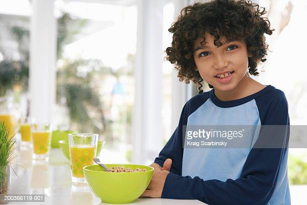 Boy (8-10) at breakfast table, smiling, portrait