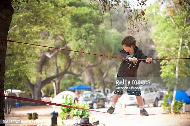 boy at campsite on slack line
