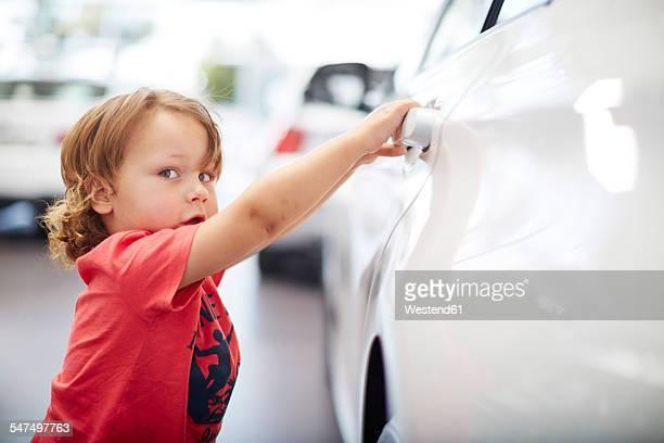 Boy at car dealer examining car