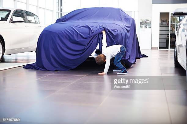 Boy at car dealer unveiling tarpaulin