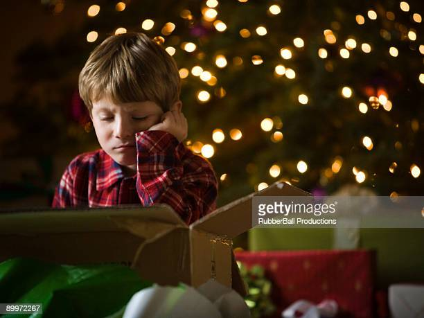 boy at christmas - disappointment stock pictures, royalty-free photos & images