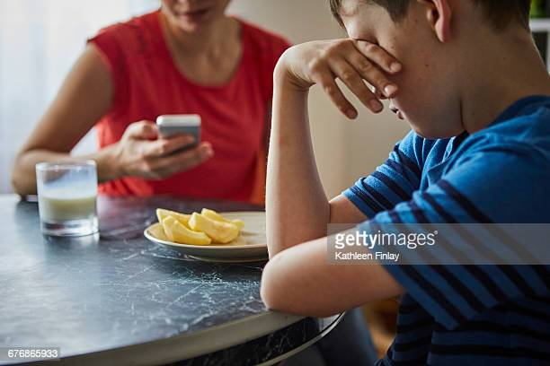 Boy at dining table, hand on eyes looking upset