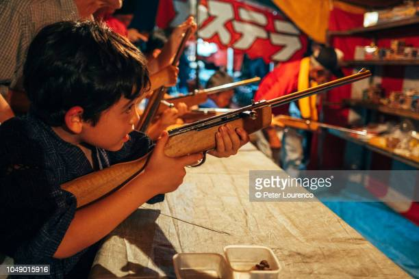 Boy at fairground shooting gallery