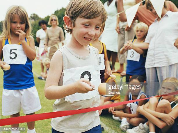 Boy (4-6) at finish line in egg and spoon race, smiling
