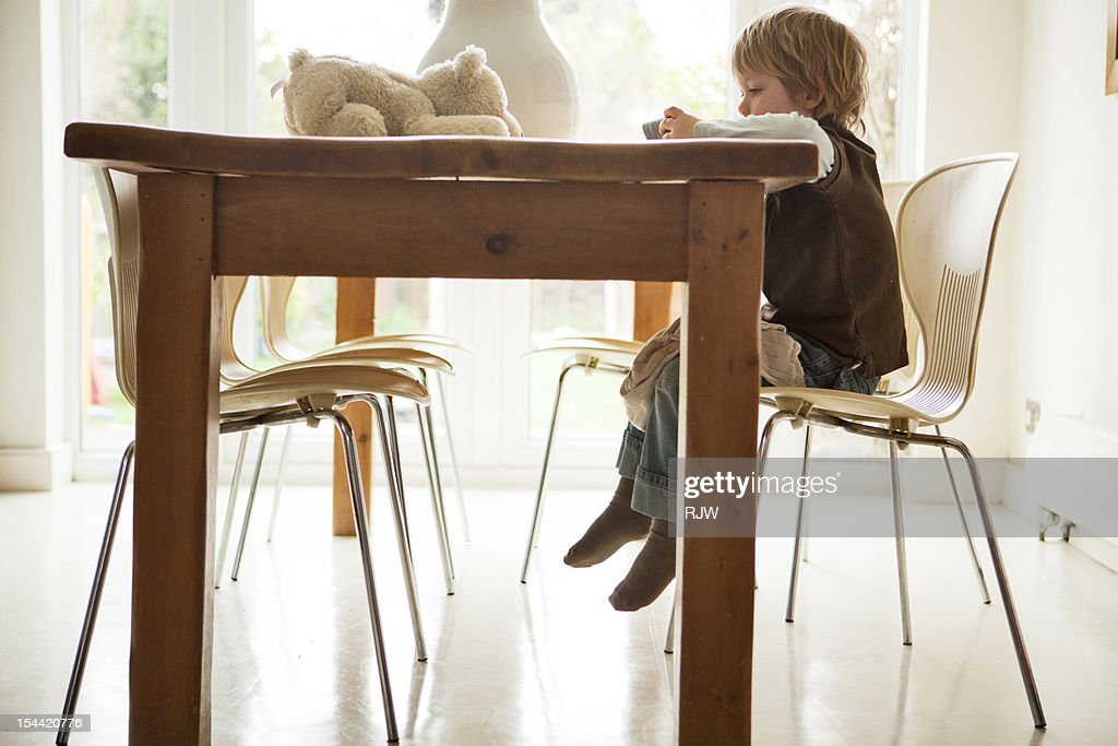 Boy at kitchen table with teddy and phone : Stock Photo