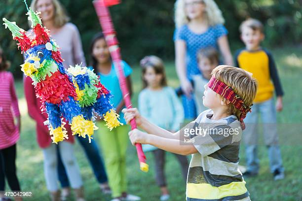 Boy at party hitting pinata with stick