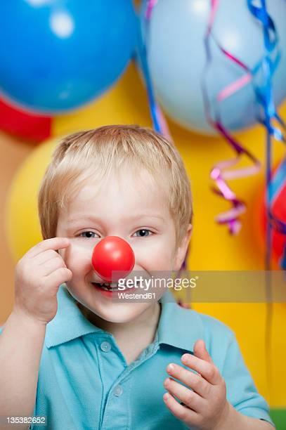 boy at party with clown's nose and balloons in background, smiling, portrait - nariz de payaso fotografías e imágenes de stock