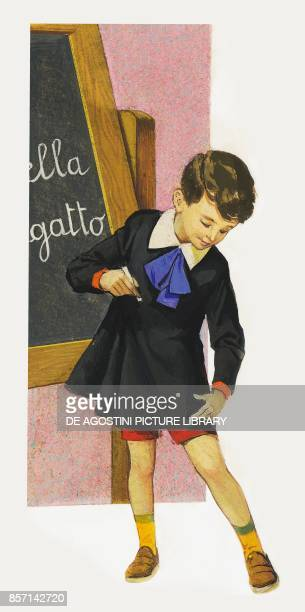Boy at school in front of the blackboard using his fingers to measure his smock to see how much he grew since the previous year drawing