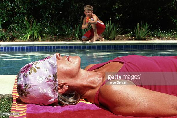 Boy at swimming pool aiming with water pistol at sunbathing woman