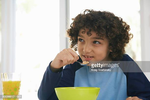 Boy (8-10) at table, eating cereal