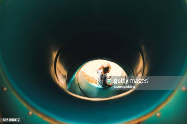 Boy at the bottom of a tunnel slide