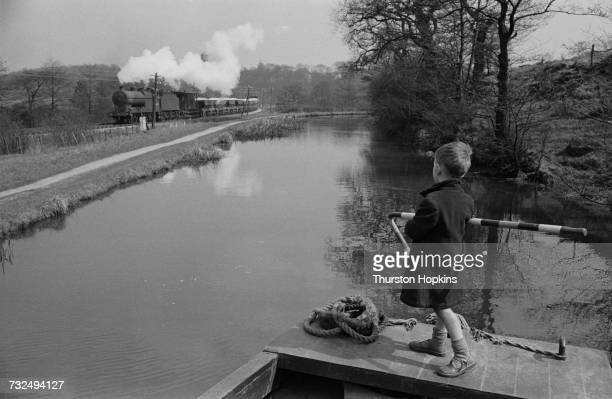 A boy at the tiller of a canal barge watches a passing freight train June 1955 Original publication Picture Post 7798 The Scandal Of Our Waterways...