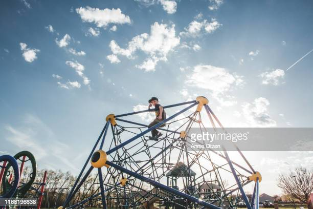 boy at the top of playground jungle gym - playground stock pictures, royalty-free photos & images