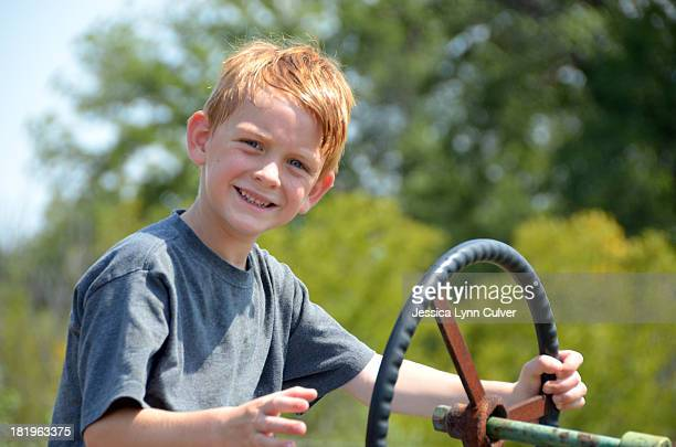 boy at the tractor wheel - ginger lynn stock pictures, royalty-free photos & images