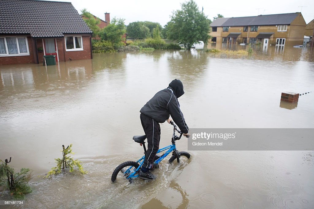 UK - Floods - Cycling through floodwaters : News Photo