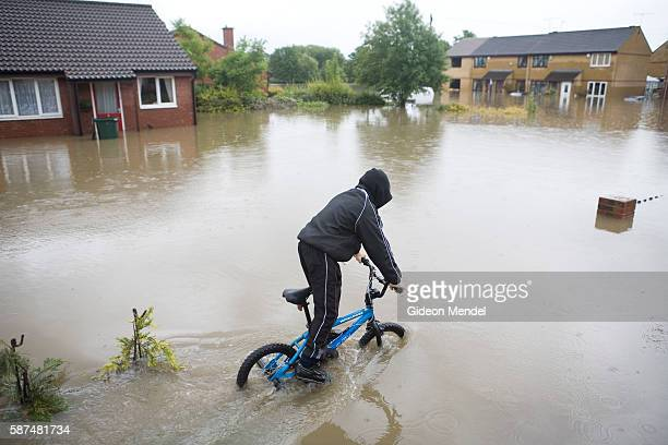 A boy attempts to cycle through the floodwaters on one of the flooded streets of Catcliffe Village This was one of the communities flooded when a...