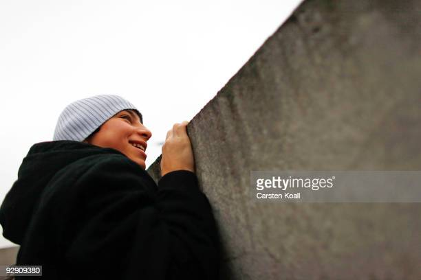 A boy attempts to peek over cracks and among roses left by visitors in a stillexisting section of the Berlin Wall into the socalled 'death strip'...