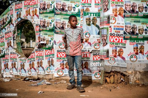 A boy awaits in front of electoral posters in support of the Peoples Democratic Party at the entrance of Tafawa Balewa Square in Ribadu Square Jimeta...