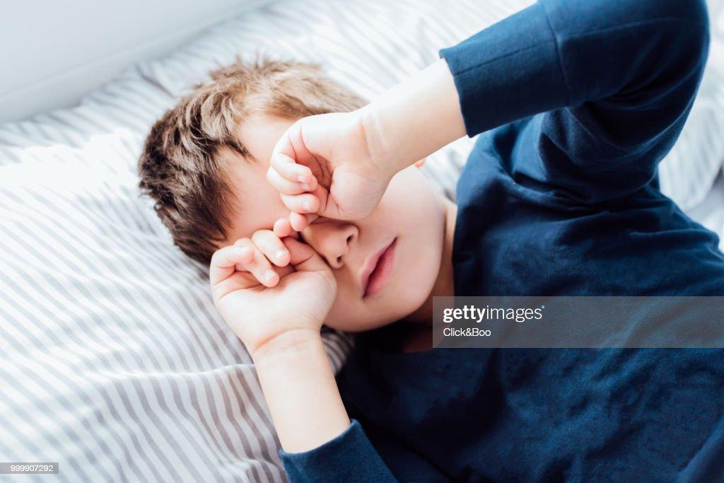 Boy awakening from a deep sleep : Stock Photo