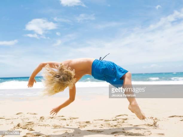 Boy (8-9) backfilling on beach