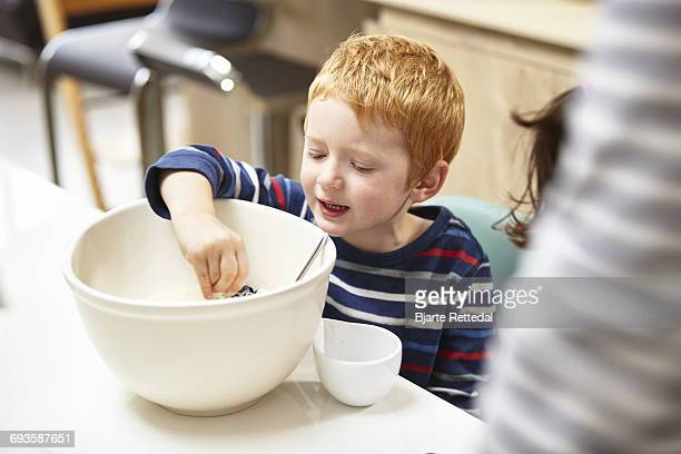 boy baking a cake - bjarte rettedal stock pictures, royalty-free photos & images