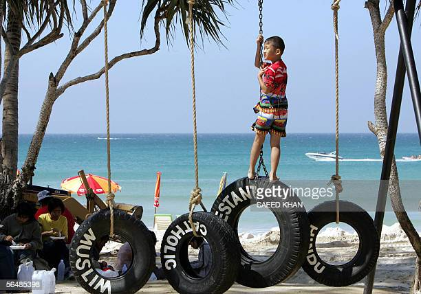 "Boy balances himself on an art piece by Italian artist Paolo Canevari at the ""Art For Andaman"" exhibition on Patong beach in Thailand's southern..."