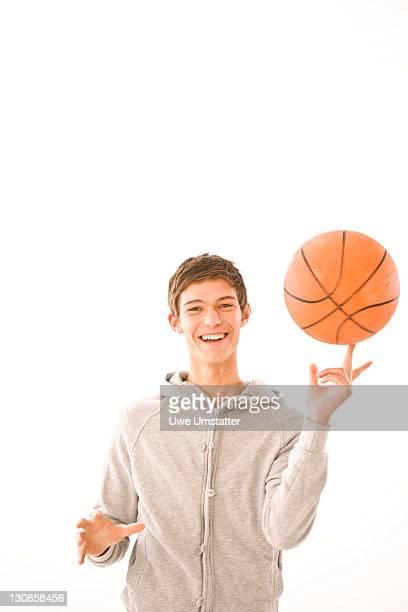 Boy balancing a basketball on his forefinger