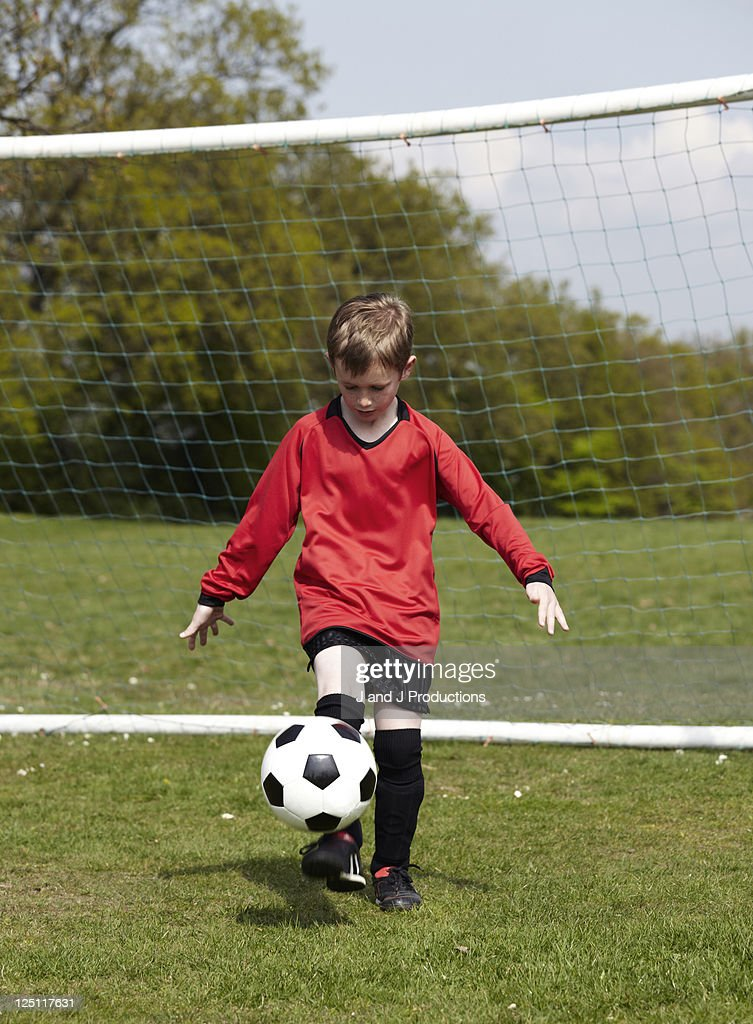Boy balancing a football : Stock Photo