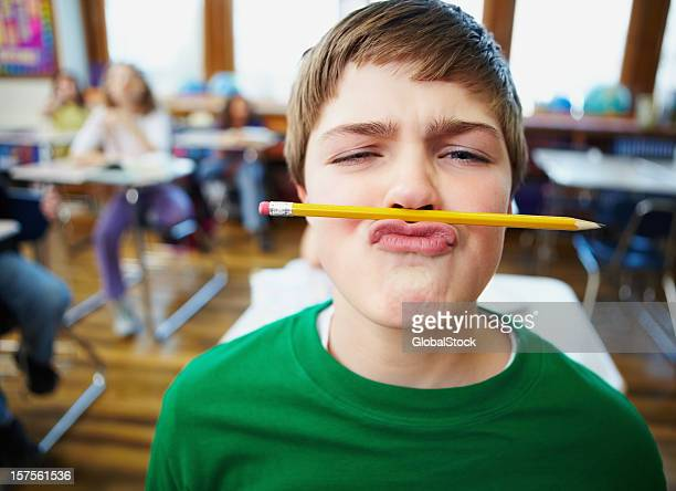 Boy balancing a pencil on his nose at school