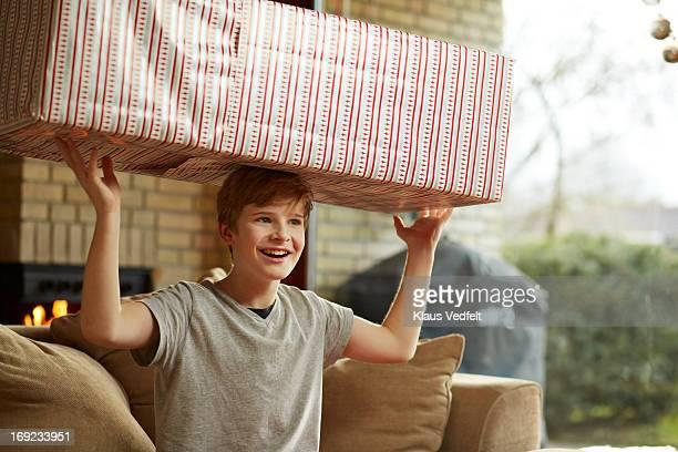 Boy balancing big christmas present on head