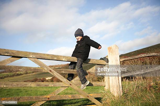 Boy balancing on a wooden gate