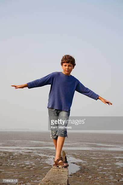 Boy (8-9) balancing on breakwater