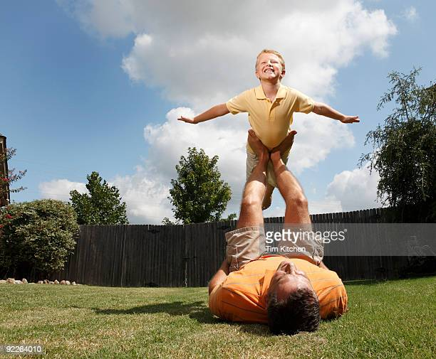 Boy balancing on father's feet, pretending to fly