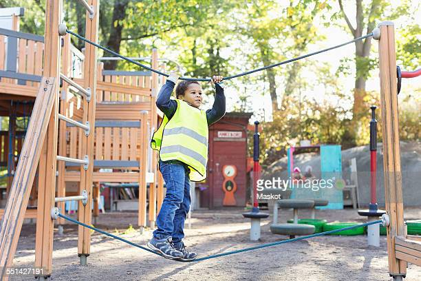 boy balancing on rope at playground - incidental people stock pictures, royalty-free photos & images