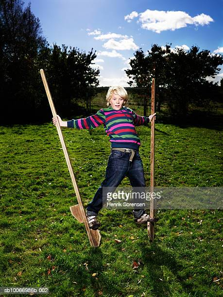 Boy (10-11) balancing on stilts