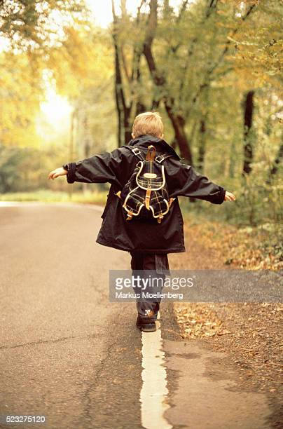 boy balancing on verge at roadside. - children only stock pictures, royalty-free photos & images