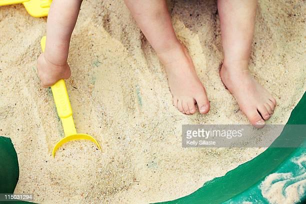 Boy barefoot in sandbox