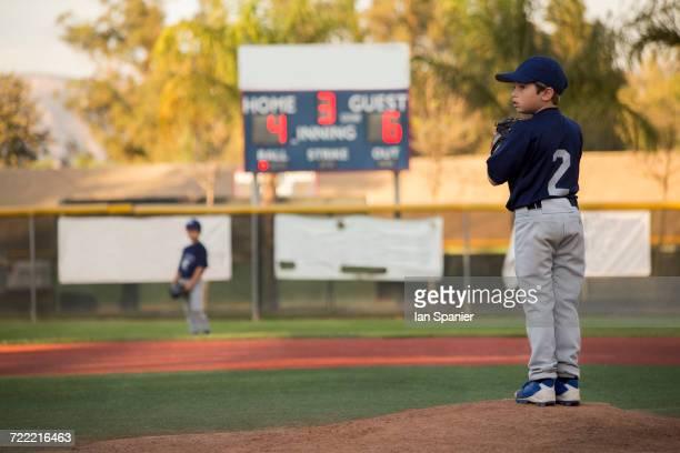 Boy baseball pitcher preparing to throw on baseball field