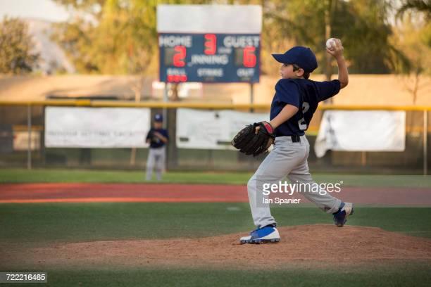 Boy baseball pitcher throwing ball on baseball field