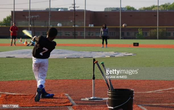 A boy bats during baseball practice at the Nationals Youth Baseball Academy in Washington DC on May 7 2018 On a searing hot summer's day in...