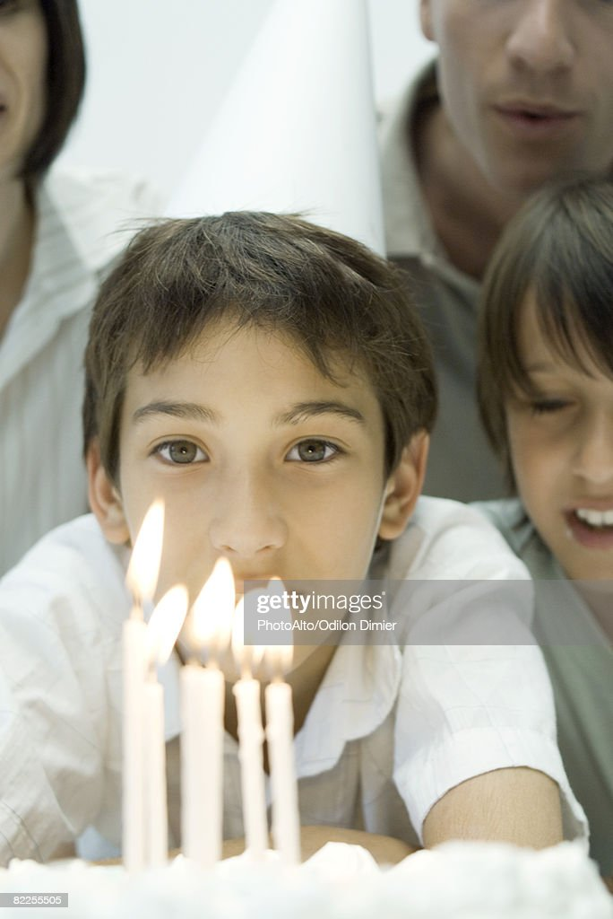 Boy behind birthday cake with lit candles, wearing party hat, surrounded by family, cropped : Stock Photo